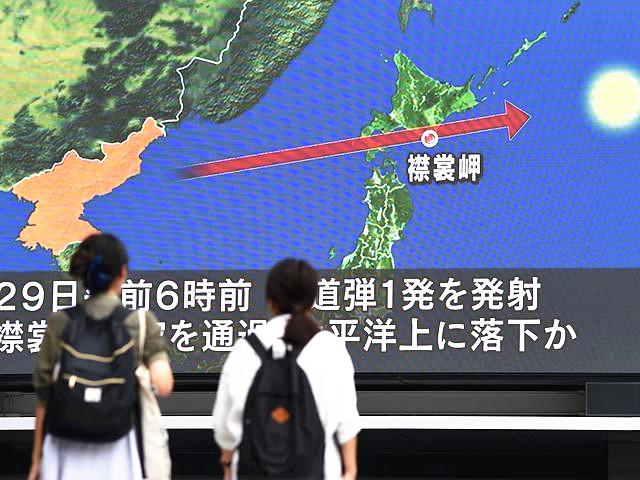显示屏显示着朝鲜导弹飞越日本北海道示意图。(新华/法新)