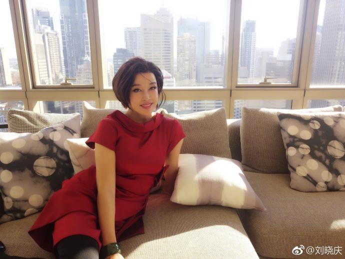 """""""照片中,刘晓庆身着一袭红裙,留着一头短发,手戴玉镯,坐在落地窗前的图片"""