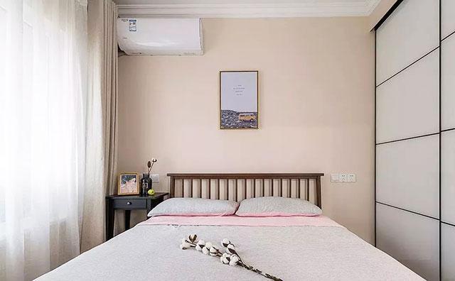 天花板安装了对称的床头吊灯,床头背景墙上挂着一黑一白两幅装饰画