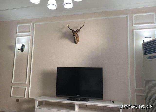 电视背景墙直接用石膏线条和墙纸进行搭配,中间有一个麋鹿头当装饰.